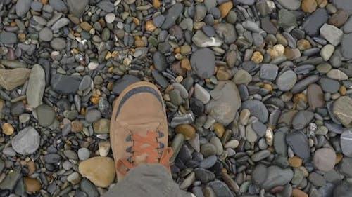 Man in Brown Sport Shoes Walks on Pebbles