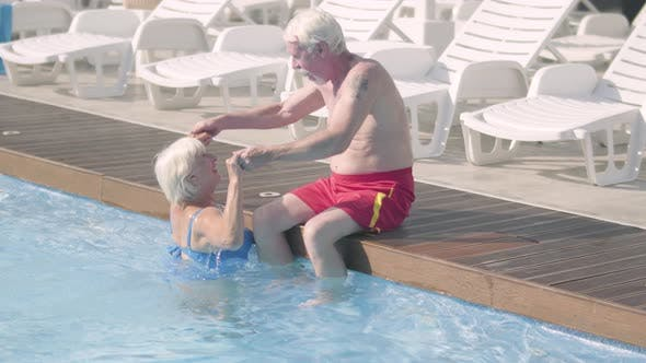 Cover Image for Happy Mature Couple Relaxing at the Pool in Hotel Complex Together