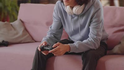 Boy Sitting on Sofa and Playing Video Game