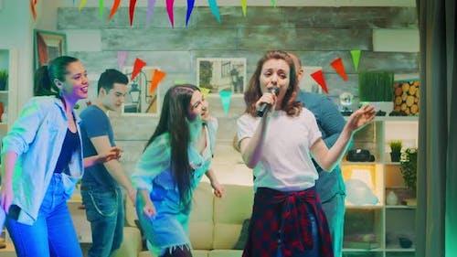 Attraktive junge Frau macht Karaoke auf der Party