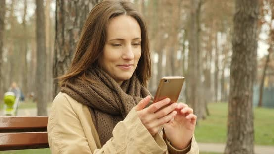 Attractive girl with cellphone scrolling and typing on touch screen socializing in social networks