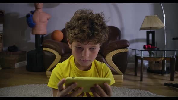 Thumbnail for Close-up Portrait of Charming Curly-haired Boy Looking at Smartphone Screen and Smiling. Caucasian