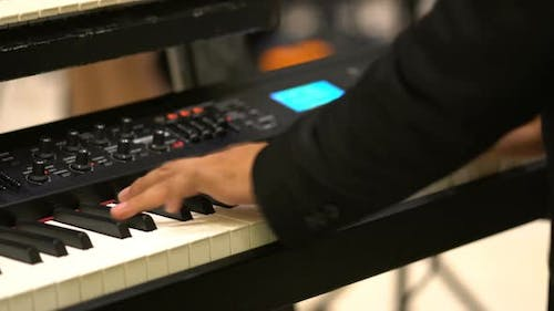 close-up musician lead electric keyboard  in live concert musical band