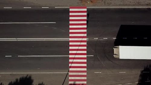 trucks are driving on the highway with a pedestrian crossing in red and white colours. Aerial view