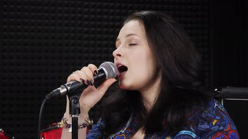 Emotional female vocal singing in microphone at recording studio