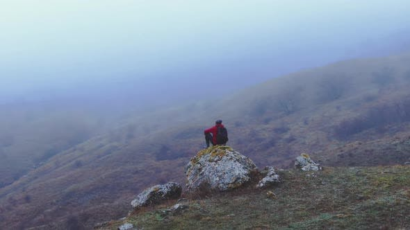 A Traveler in a Red Jacket Sits on a Stone Against a Background of Mountains