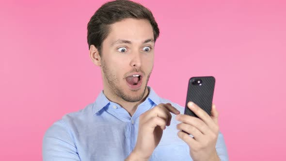 Thumbnail for Wow, Surprised Young Man Using Smartphone on Pink Background