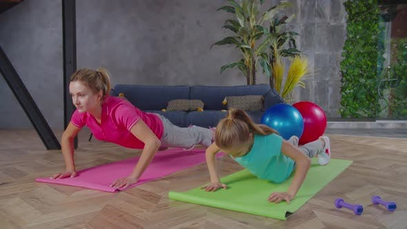 Sporty Fit Mom and Girl Doing Push Ups Together at Home