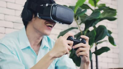 A handsome man playing the game using VR glasses on a sunny day.
