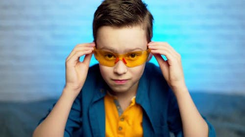 A teen boy putting on medical yellow glasses as a protection against virus disease.