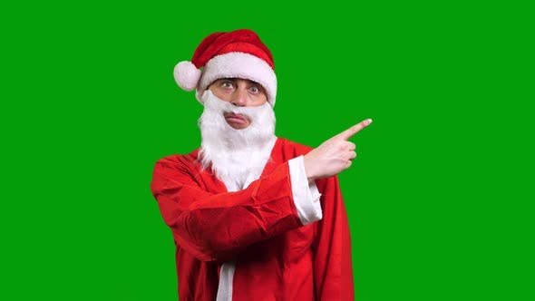 Santa Claus in Red Suit Pointing Aside on Green Chroma Key Background