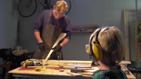 Boy Looks at Working Man in the Workshop