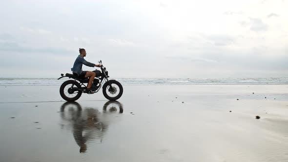 Man in Riding Motorcycle on Beach. Vintage Motorbike on Beach Sunset on Bali