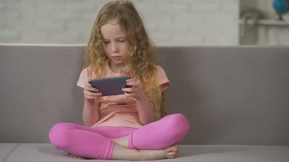 Thumbnail for Blond Curly-Haired Child Relaxing on Sofa and Playing on Smartphone Addiction