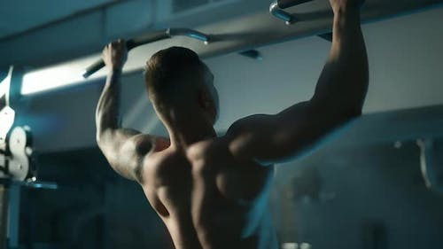 A Handsome Young Muscular Sportsman is Doing Exercise on a Fitness Machine in the Gym