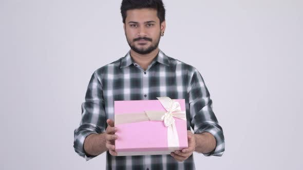 Thumbnail for Portrait of Young Happy Bearded Indian Man Giving Gift Box