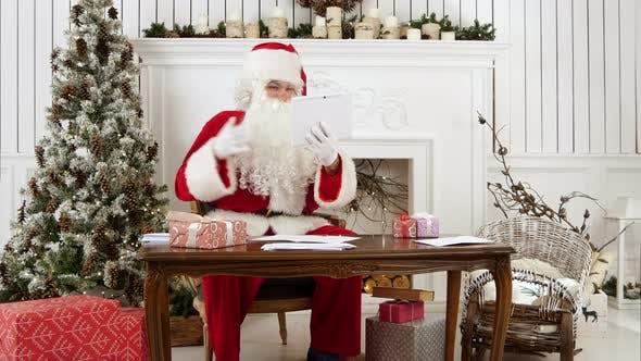 Thumbnail for Santa Claus Cheerfully Talking Via Tablet