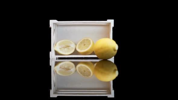 Thumbnail for Yellow lemon rolling against white crate with halves of lemons inside