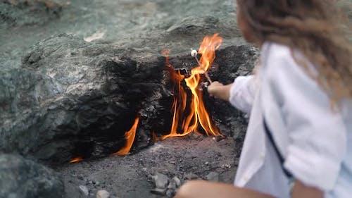 Slim Woman Roasts Marshmallows Over Chimaera Mountain Fire