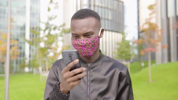 Thumbnail for A Young Black Man in a Face Mask Reads Positive News on a Smartphone and Nods - Office Buildings
