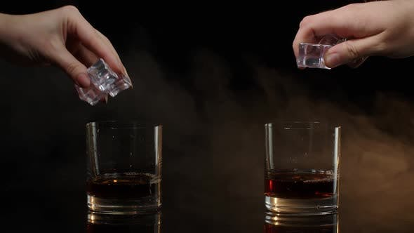 Barmans Dropping Ice Cubes Into Drinking Glasses with Whiskey Cognac Brandy on Black Background