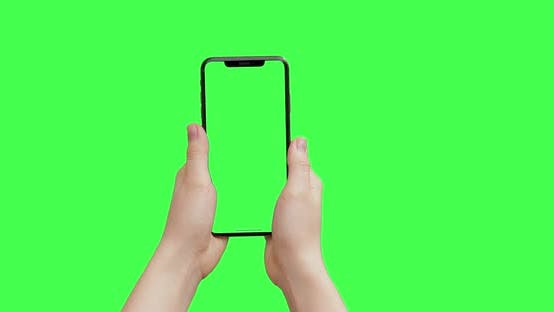 Thumbnail for Girl hands holding the smartphone on green screen chroma key background. iPhone mock-up copy space