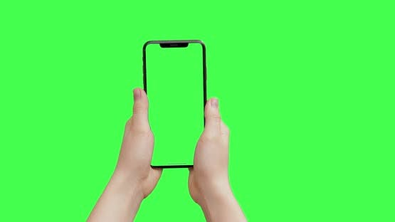 Girl hands holding the smartphone on green screen chroma key background. iPhone mock-up copy space