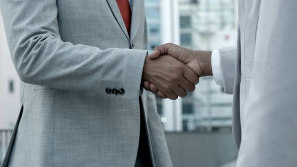 Thumbnail for African American Colleagues Shaking Hands on Street