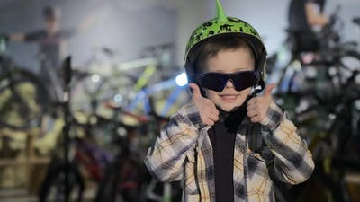 Funny Kid with Sunglasses and Helmet Shows Thumbsup in Shop