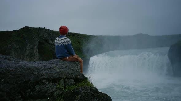 Thumbnail for Man in Wool Sweater on Edge of Waterfall Rock