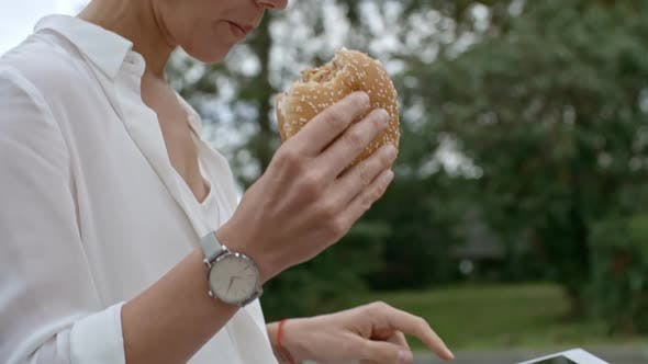 Thumbnail for Business Lady with Tablet Eating Burger Outdoors