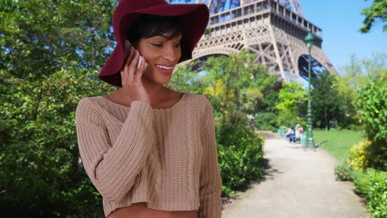 Thumbnail for Young African-American female near Eiffel Tower calls home on cellphone