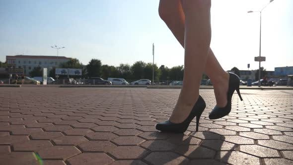 Female Legs in High Heels Shoes Walking in the Urban Street. Feet of Young Business Woman in High
