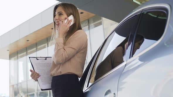 Thumbnail for Lady Broker With Contract Talking With Client on Smartphone, Standing Near Car