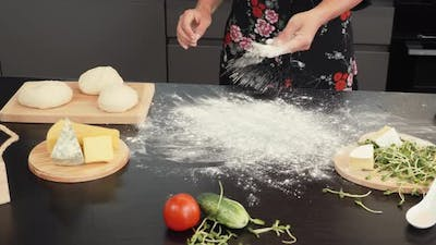 Sprinkling flour on table in kitchen. Woman cook sprinkles flour on wooden table in bakery