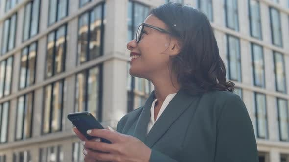 Cheerful Businesswoman Using Cellphone Outside