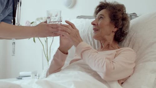 Home Caregiver Helping Elderly Woman Drink Water