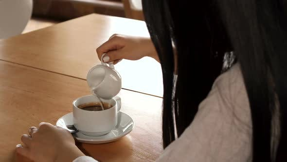 Thumbnail for Girl Adds Cream Into Her Coffee at the Cafe