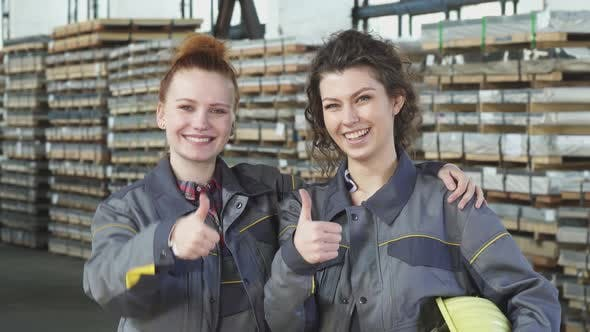 Two Happy Female Factory Workers Embracing Showing Thumbs Up at the Storage
