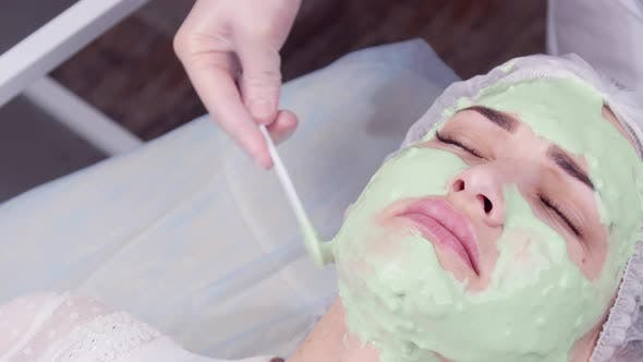 Beauty and Cosmetology Concept. Young Woman with Cream Mask in a Beauty Parlour