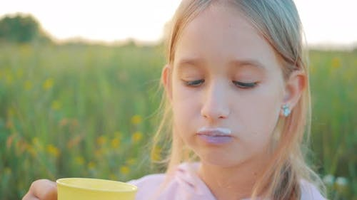 Cute Little Girl in the Field Eating a Bread and Drinking Milk at Sunset. Healthy Eating Concept