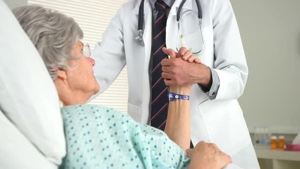 Thumbnail for Elderly woman holding her doctor's hand