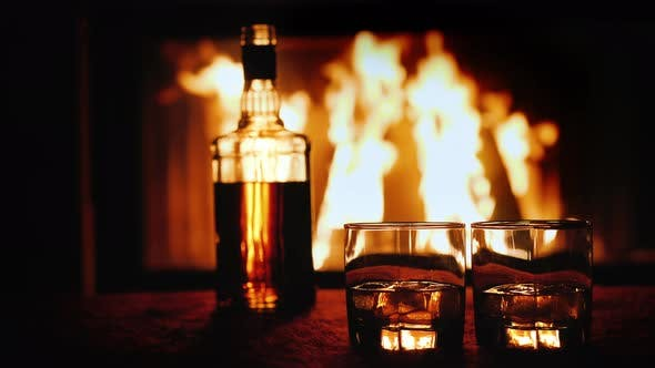 Cover Image for Two Glasses and a Bottle of Whiskey Stand on the Table Against the Background of a Hot Fireplace