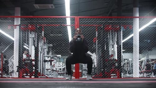An Africanamerican Sportive Woman Squatting with Weight in a Gym