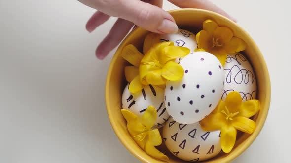 Thumbnail for Gelbe Tasse auf weißem Hintergrund mit Ostereiern. Weibliche Hand Entfernt eine Tasse mit Eiern aus dem