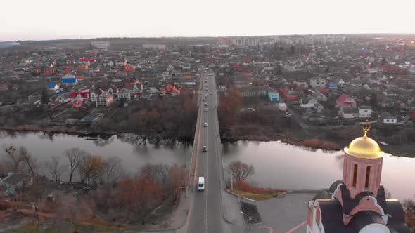 Pull Away Aerial Shot of Bridge Near River and Two Churches in Small European City