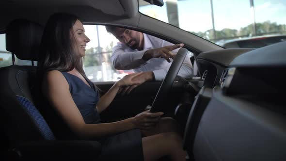 Thumbnail for Cheerful Young Woman Sitting in Auto at Dealership