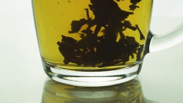 Thumbnail for Black Tea Particles Spinning at Bottom Transparent Glass Mug Creating a Whirl, Brewing Tea Slow