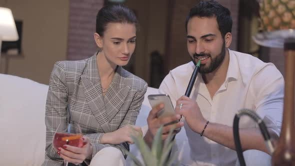 Man And Woman Smoking Shisha, Drinking Cocktails And Using Phone