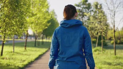 Woman in Sports Jacket Walking in Park in the Morning
